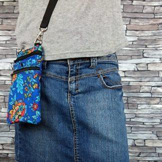 Schoudertasje van een leuke blauwe print om je telefoon, sleutels, portomonnee, ID kaart, geld mee te nemen. Er zijn drie zakken, twee met (sterke) rits en in het midden een inschuifzak om snel je telefoon te kunnen pakken. Als je hem veiliger wilt kun je hem in de grootste zak met rits stoppen. Het tasje is 21 x 13 cm. De binnenmaten van de zaken zijn: 19 x 13 (met rits) 17 x 13 cm (inschuifzak) 14 x 13 cm (met rits) Binnenin heeft deze tas sterke denim stof. De schouderband meet 70 tot 130 cm, aan te passen met een schuifgesp. Ik kan ook een extra groter schouderband van 100 - 200 cm maken, voor extra grote maten. Dit is gemeten als de cirkel om je lichaam. Wil je het tasje groter of kleiner, stuur me een berichtje,. Voor kleinere aanpassingen vraag ik geen extra geld, ik knip het patroon gewoon wat groter of kleiner.